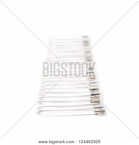 Line border made of multiple metal safety pins isolated on white background