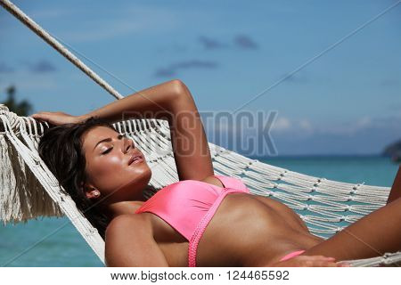 Young woman swinging in hummock on blue sea background