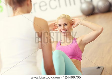 Picture of fit woman doing sit ups in gym