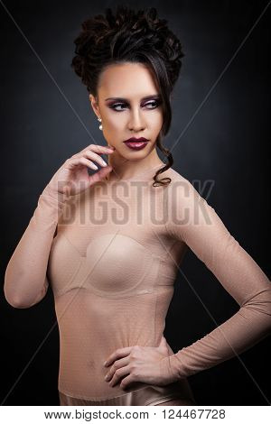 Sexy brunette lady posing on dark background