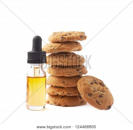 Oil essence in a glass bottle next to the pile of cookies isolated over the white background