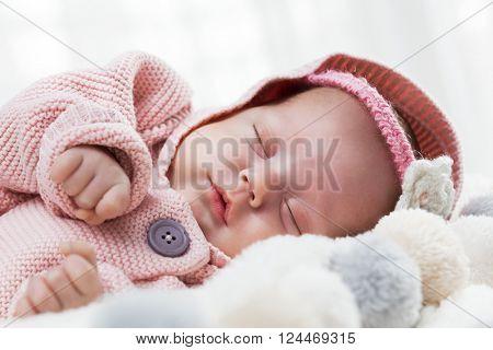 Newborn baby sleeping on white fur blanket. White background.