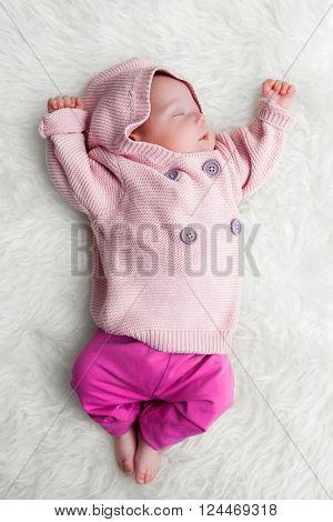 Newborn baby sleeping on white fur blanket. White background, full body shot