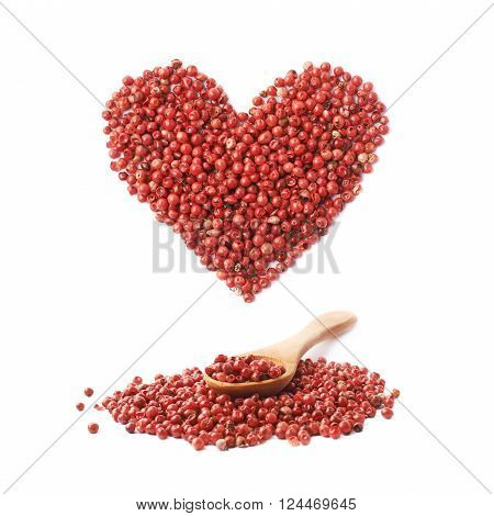 Wooden spoon over the pile of the red pepper seeds and heart shape over it, composition isolated over the white background