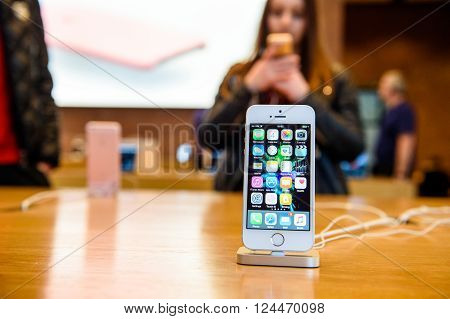 PARIS FRANCE - APR 4 2016: People testing new iPhone with the Apple iPhone SE in docking station during the sales launch of the latest Apple Inc. smartphone and iPad Pro at the Apple store in Paris France