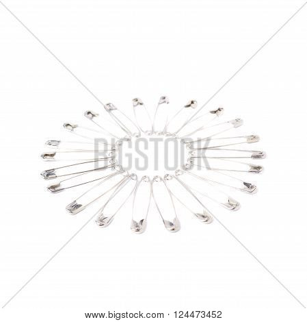 Round frame made of metal safety pins isolated on white background