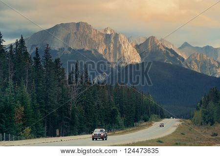 Highway in Banff national park at sunset with mountains and forest in Canada.