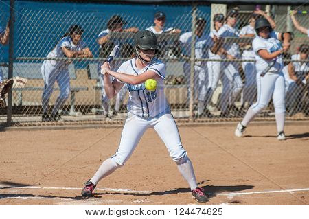 High school softball player taking the high pitch.