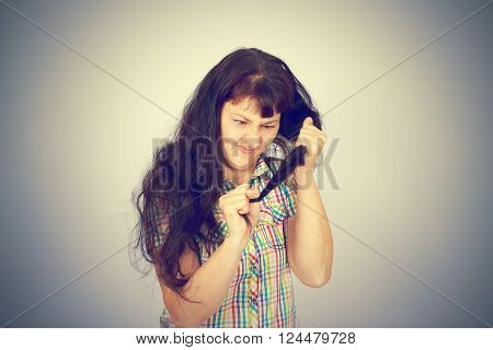 young woman looks at her problematic hair. On gray background.