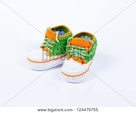 Little baby shoes. Hand knitted sneakers for newborn boy or girl. Crochet handmade bootees on white background.