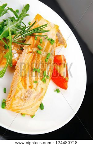savory sea fish : roasted salmon fillet garnished with green rocket leaves and tomatoes on black dish isolated over black background