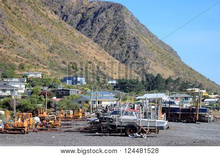 Ngawi, New Zealand - 13 January 2016: Fishing boats and tractors on the beach at the small fishing village of Ngawi, New Zealand.