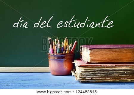 the text dia del estudiante, students day written in spanish in a chalkboard, placed on a blue rustic wooden school desk next to some old books and a pot with some pencils