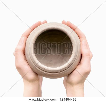 Close view of unburnt clay pot in a woman's hands isolated on white background