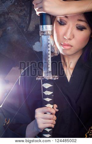 beautiful Asian girl in kimono with a katana