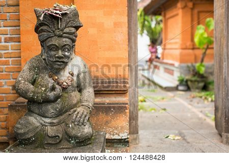 Traditional demon guard statue carved in stone on Bali, Indonesia.