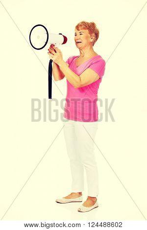 Senior smiling woman screaming through a megaphone