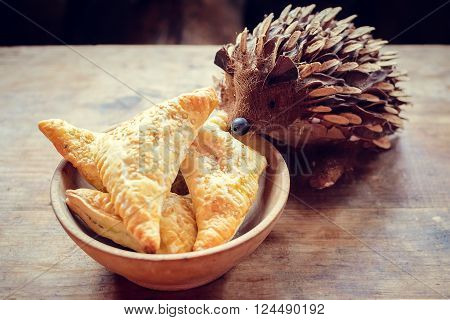 Wooden bowl of freshly baked homemade pastry with jag on an old barn wood table with hedgehog. Rustic background.