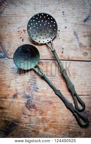 Vintage kitchen utensils on rustic wood background. Vintage silverware on rustic wooden background. Closeup natural side-lighting for effect. Vertical. Top view.
