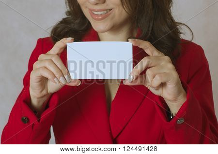 A young woman between 30 and 40 years old dressed in a classical red jacket keeps a white card with free space for a text.