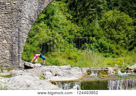 Woman meditating in yoga bridge pose under a medieval stone bridge near river in beautiful mountains. Motivation and inspirational stay fit and exercise. Healthy lifestyle outdoors in nature fitness concept.