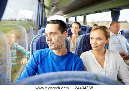 transport, tourism, road trip and people concept - happy couple with group of happy passengers or tourists in travel bus