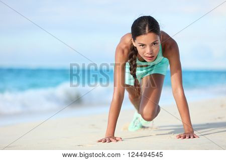 Fitness athlete working out body core with bodyweight exercises. Strong fit woman training cardio and exercising abdominal muscles with mountain climber workout exercise on beach.
