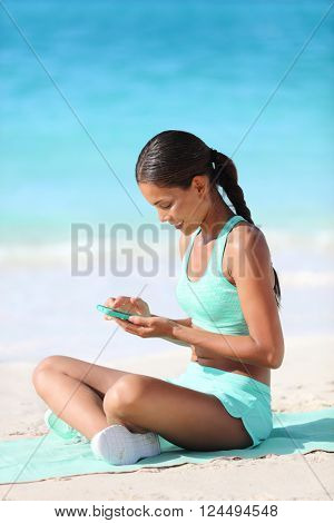 Fit girl using fitness app on phone during travel holidays on beach texting or posting on social media online. Healthy sporty Asian woman living a happy active life exercising on towel.