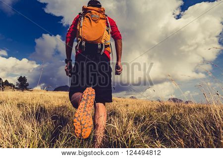 Hiking man or trail runner walking in mountains. Travel in Italy Europe. Fitness and healthy lifestyle outdoors in fall autumn nature