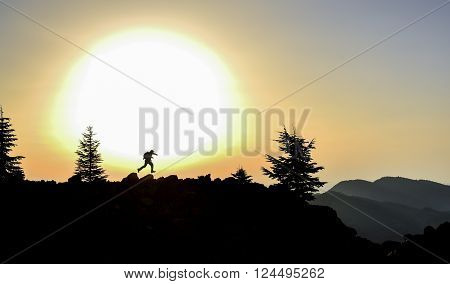 man running at sunrise summit.happiness in the mountains at the top.