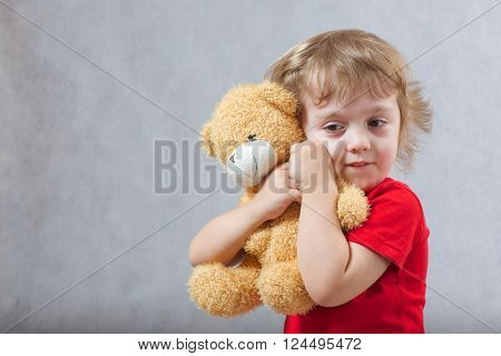 A child of 3 years old with long hair hugs a brown plush teddy bear on a gray background