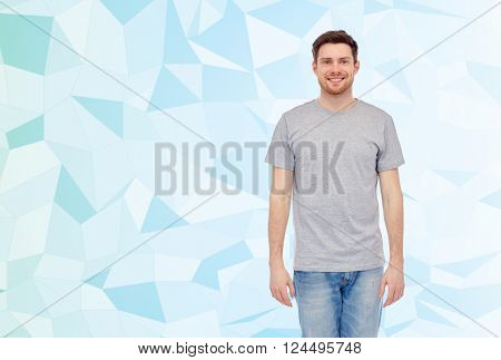 male, gender, fashion and people concept - happy smiling young man in gray t-shirt and jeans over blue low poly texture background,