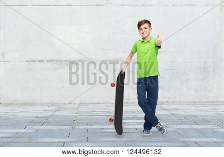 childhood, leisure, school and people concept - happy smiling boy with skateboard showing thumbs up over concrete gray wall on city street background