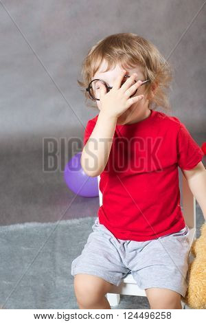 A Child Covers Its Face With A Palm