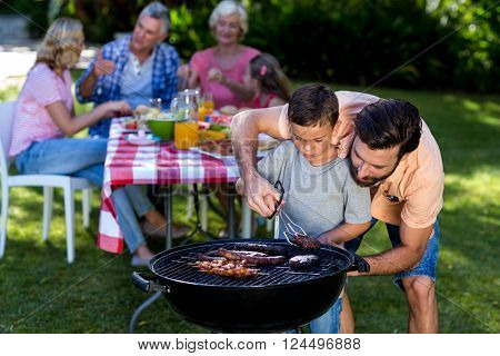 Father teaching son cooking on barbecue with family in background