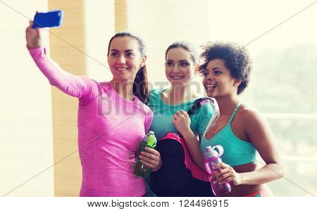 fitness, sport, training, gym and lifestyle concept - group of happy women with bottles and smartphone taking selfie in gym