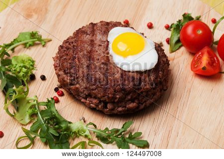steak egg cutlet on a wooden board tomatoes arugula salad bright beautiful quail beef pork
