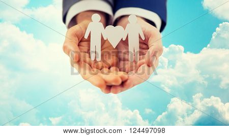 people, homosexuality, same-sex marriage and love concept - close up of happy male gay couple holding paper cutout love symbol over blue sky and clouds background