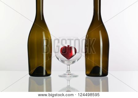 Two bottles and red heart inside a glass of cognac on a glass plate
