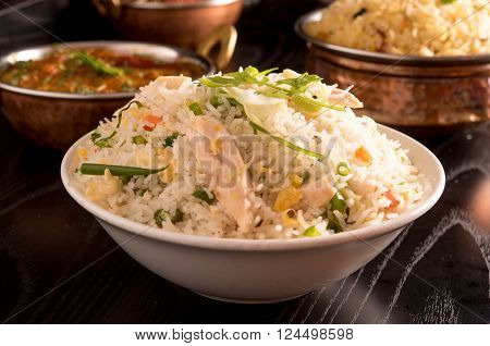 fried rice in a white bowl with biriyani and curry
