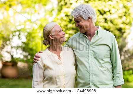 Smiling senior couple looking each other while standing in yard