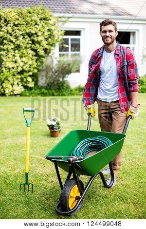 Portrait of smiling man holding rake in yard