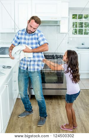 Father with mobile phone wiping container while daughter pulling him at kitchen