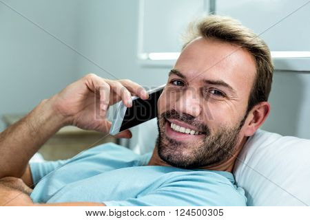 Close-up portrait of happy man talking on mobile phone while relaxing on bed at home