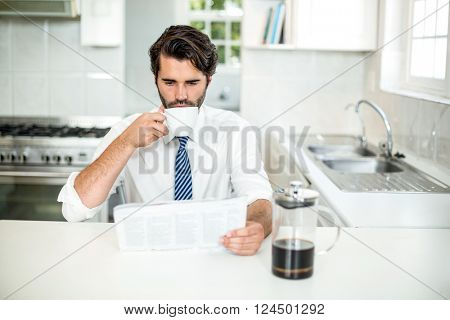 Businessman reading newspaper while drinking coffee at table in kitchen