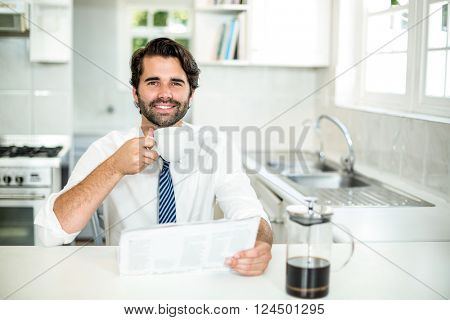 Portrait of confident businessman drinking coffee while reading newspaper in kitchen