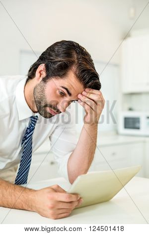 Close-up of tensed businessman looking at digital tablet by table in kitchen