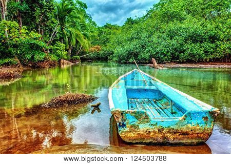 Old boat in tropical river, perfect place for fishing, exotic summer adventure, amazing nature of National Park of Costa Rica, Central America