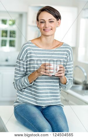 Portrait of happy beautiful woman with coffee sitting on worktop in kitchen at home