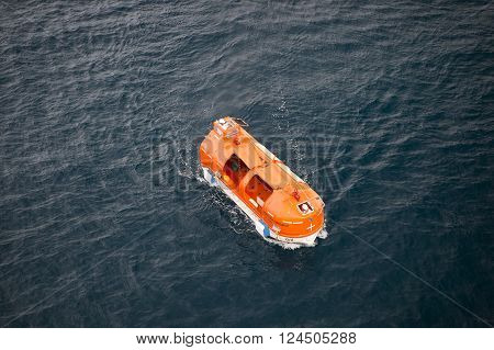 st .Barts , France - November 19, 2015: Orange cruise ship life boat sailing next to st .Barts on dark water